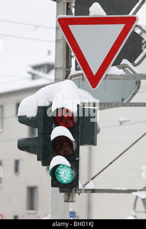 snow-covered traffic lights and yield sign - Stock Photo