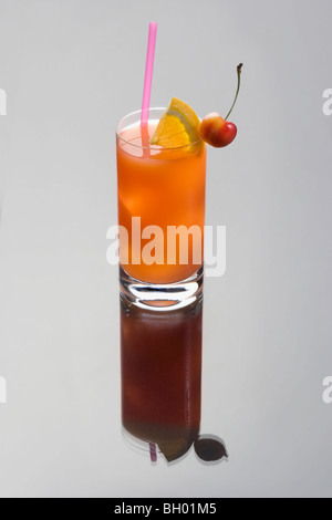 Seabreeze mixed drink with lime and cherry garnish on a gray background - Stock Photo