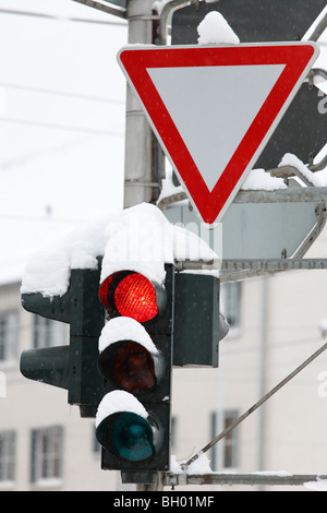 snow-covered traffic lights with yield sign - Stock Photo
