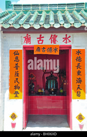Interior shot, through open doors, of a small Buddhist shrine, western end of Stanley Market, Stanley, Hong Kong, - Stock Photo