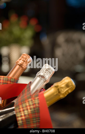 Three champagne bottles one silver two gold red ribbons metal bowl blurred background interior view blurred background - Stock Photo