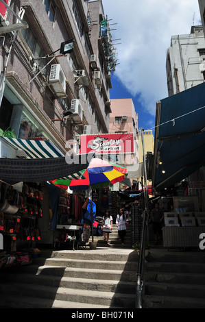 Chinese women walking down ladder alley steps past open air luggage and artwork shops, Stanley Market, Stanley, - Stock Photo