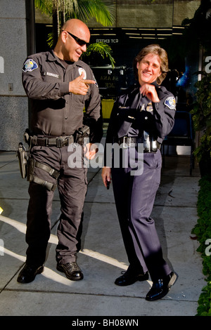 A member of Santa Ana, California Police Department SWAT (Special Weapons and Tactics) team jokes with a female - Stock Photo