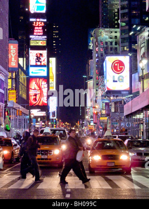 Traffic stops for pedestrians at night on Seventh Avenue in New York's Times Square with its bright outdoor signs. - Stock Photo