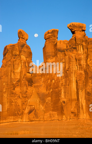 Near full moon along with the Three Gossips, Arches National Park, near Moab, Utah. - Stock Photo