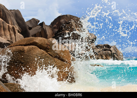 Wave breaking against a rock in the Seychelles. Fast shutter speed used to freeze the water droplets - Stock Photo