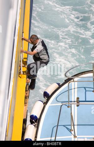 The pilot climbing the latter. - Stock Photo