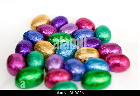 A selection of colorful mini chocolate Easter eggs on a white background - Stock Photo