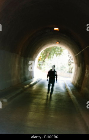 Mysterious blurred male figure walking in tunnel. - Stock Photo