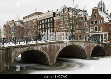 Bridge and houses on frozen Keizersgracht canal in Amsterdam - Stock Photo