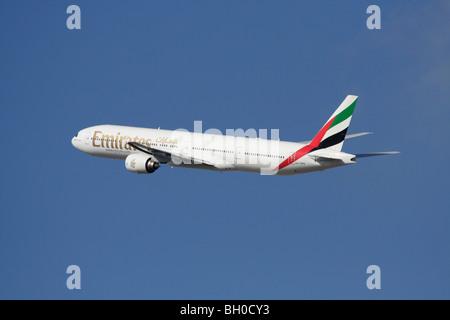 Emirates Boeing 777-300 long-haul passenger jet plane in flight against a blue sky - Stock Photo