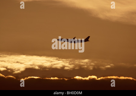 Commercial air travel. Jet plane flying in cloudy sky at sunset. Silhouette of airplane in flight. - Stock Photo