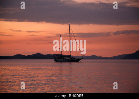 Moored yacht at  sunset Donje Celo harbour, Kolocep, South Dalmatia Croatia one of the Elaphite islands near Dubrovnik - Stock Photo