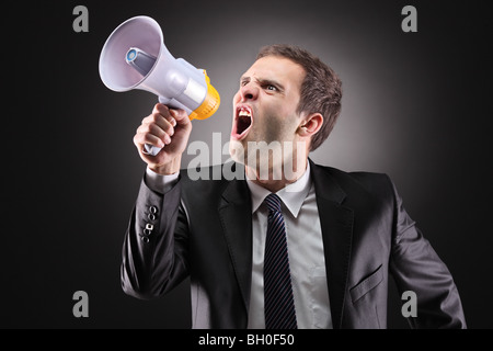 Businessman shouting on a megaphone - Stock Photo