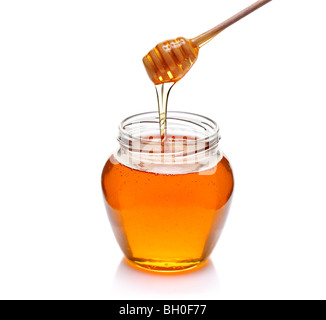 Honey bowl and a drizzler isolated on white - Stock Photo