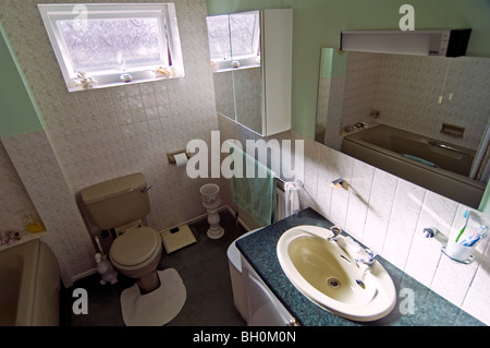Horizontal wide angle interior of an old-fashioned 80's bathroom with a green coloured bathroom suite. - Stock Photo