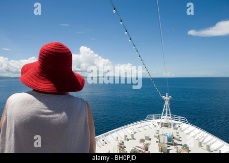 Woman wearing red hat and bow of MV Columbus in the sunlight, Mamanuca Archipelago, Fiji Islands, South Pacific, - Stock Photo