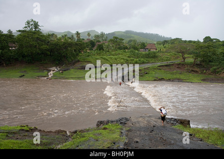 Floodwater river flooding a road at Nausori Highland, Navala, Viti Levu, Fiji Islands, South Pacific, Oceania - Stock Photo