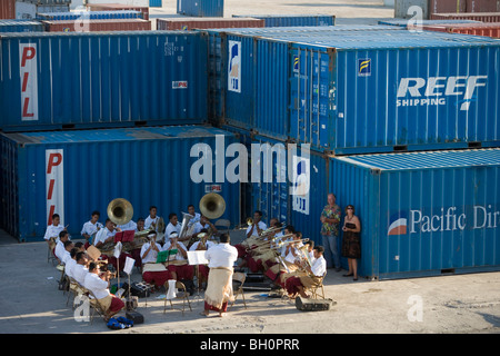 Tongan Brass Band playing amidst containers at harbour, Nuku'alofa, Tongatapu, Tonga, South Pacific, Oceania - Stock Photo