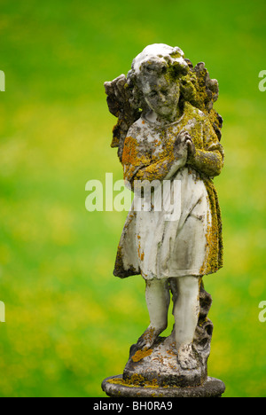 Marble Angel sculpture folding its hands, covered with lichen, Rossura, valley Leventina, Ticino, Switzerland - Stock Photo