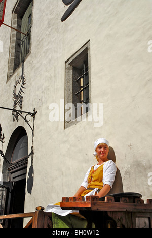 Waitress in front of Olde Hansa Restaurant, which serves medievel dishes, Tallinn, Estonia - Stock Photo