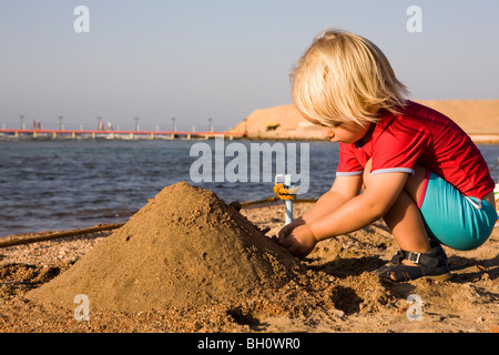 Little child, girl, 3, playing with sand on the beach of the Lamaya Resort, Coraya, Marsa Alam, Red Sea, Egypt - Stock Photo