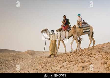 A man, a bedouin leading two camels with tourists, a mother and two children, Marsa Alam desert, Red Sea, Egypt - Stock Photo