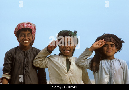 Bedouin boys happily posing for the camera in the Wahiba Sands of Oman. - Stock Photo