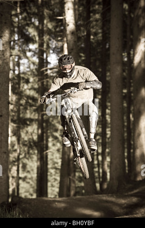 A teenager on his mountain bike during a jump, Downhill Park, Wagrain, Austria - Stock Photo