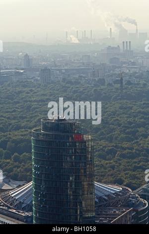 View at DB Tower and smoking chimney stacks, Berlin, Germany, Europe - Stock Photo