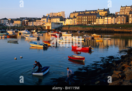 Boys rowing in the harbour in the evening, Portrush, County Antrim, Ireland, Europe - Stock Photo