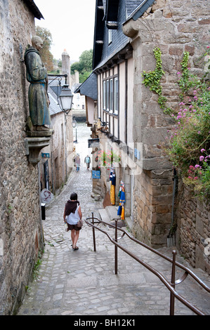 A tourist wanders down Rue Neuve the narrow and steep cobbled alley way leading down to the old port of Saint Goustan - Stock Photo