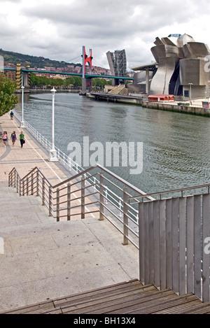 View of Guggenheim Museum, Bilbao from opposite bank of River Nervión, showing riverside-walk with people walking - Stock Photo
