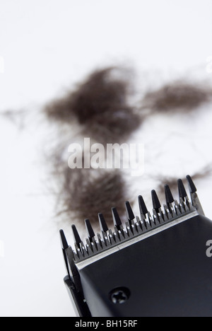 hair clippers close-up and hairs in the background - Stock Photo