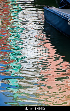 Colorful reflections from the homes line the canals in Burano an island near Venice Italy - Stock Photo