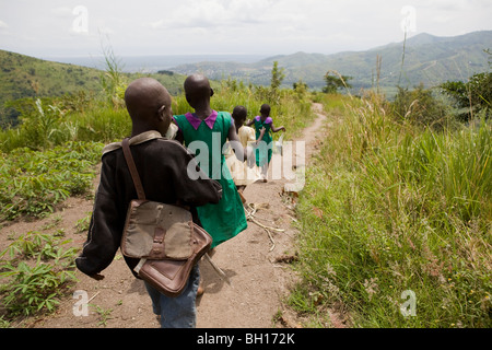 Children walking home after school in mountains in Uganda - Stock Photo