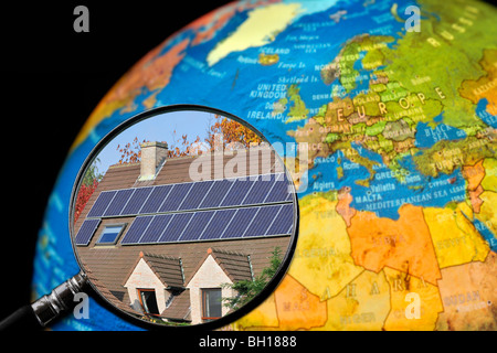 Photovoltaic solar panels / cells on roof of house seen through magnifying glass held against illuminated terrestrial - Stock Photo
