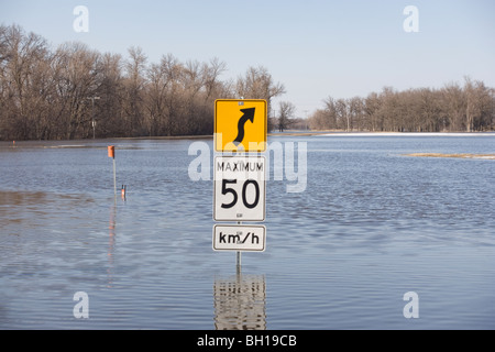 Road sign on road that is covered with floodwater from the Red River, Manitoba, Canada - Stock Photo