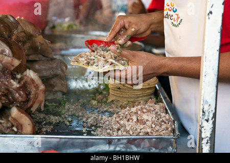 hands of a man making pork tacos at a street stall with one taco in progress & ingredients below on trays in Oaxaca - Stock Photo