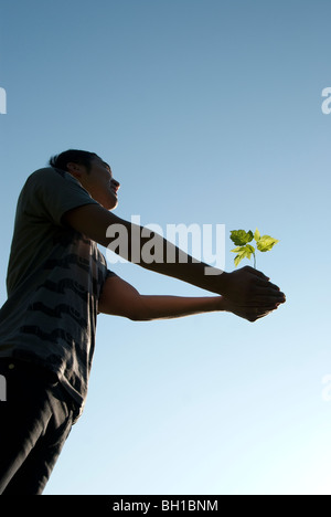 Young man holding seedling with outstretched arms, Assiniboine Park, Winnipeg, Manitoba, Canada - Stock Photo