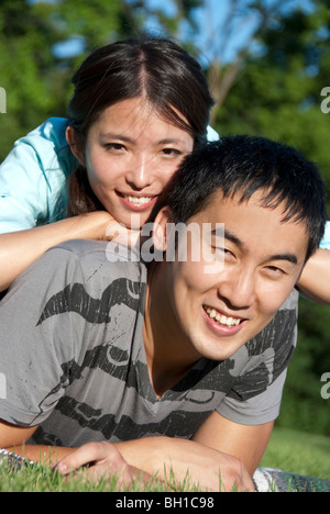 Portrait of young couple lying on grass, Assiniboine Park, Winnipeg, Manitoba, Canada - Stock Photo