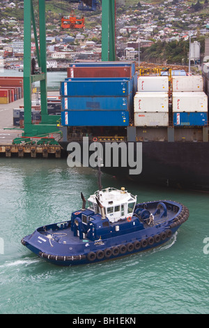 A tug arrives at the stern of a container ship ready to assist the ship depart from port - Stock Photo
