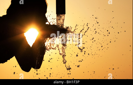 Silhouette of an Indian girl drinking from a water pump. India - Stock Photo