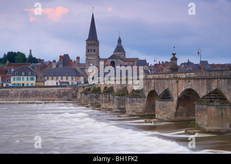 Evening in the old town of La-Charité-sur-Loire, Stone bridge over the Loire river, Church and former monastery - Stock Photo