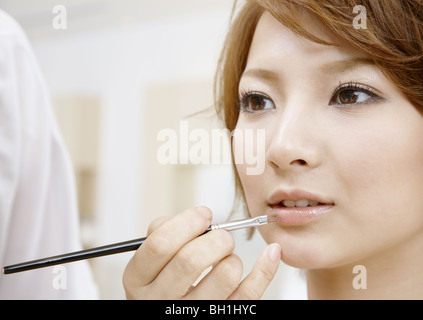 A young woman getting her makeup done - Stock Photo