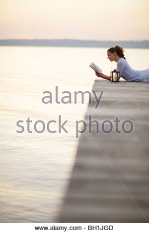 Woman lying on jetty at lake Starnberg while reading a book, Ambach, Bavaria, Germany - Stock Photo