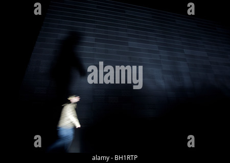 Person walking past a wall at night, Oslo, Norway - Stock Photo