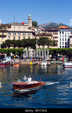View over Lake Lugano to Luganow with cathedral St. Lorenzo, small motorboat in foreground, Lugano, Ticino, Switzerland - Stock Photo