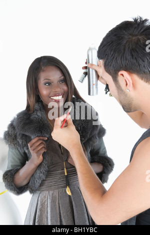 Hair stylist makes adjustments to model in fake fur jacket - Stock Photo