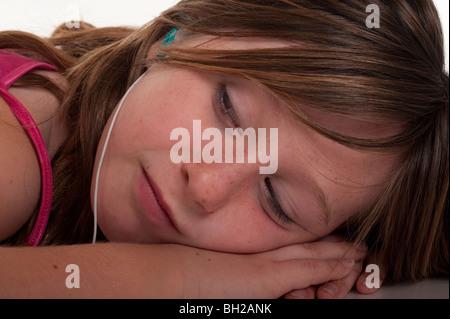 little girl listening to music through earphones - Stock Photo